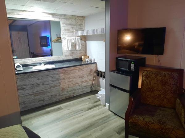 Coachlight Inn vanity and sink, chair, tv, mini fridge, and microwave